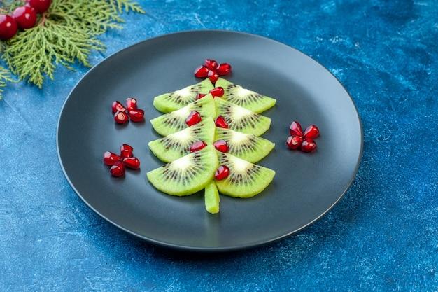 Vooraanzicht vers gesneden kiwi's met granaatappels in plaat op blauw oppervlak zacht sap kleur exotisch tropisch fotofruit