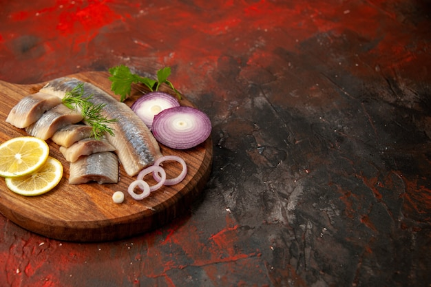 Vooraanzicht vers gesneden vis met uienringen en citroen op donkere maaltijd vlees zeevruchten snack kleurenfoto gratis plaats