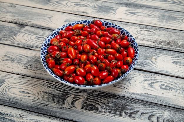 Vooraanzicht vers rood fruit rijpe en zure bessen binnen plaat op het grijze rustieke oppervlak fruit bes kleur vitamine boom plant