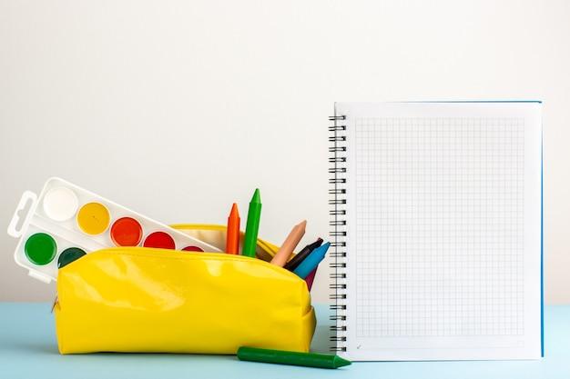 Vooraanzicht verschillende kleurrijke potloden in gele pennendoos met voorbeeldenboek op het blauwe bureau