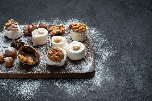 Vooraanzicht verschillende koekjes met cakes en walnoten op het donkergrijze oppervlak cake biscuit suiker bak zoet koekje