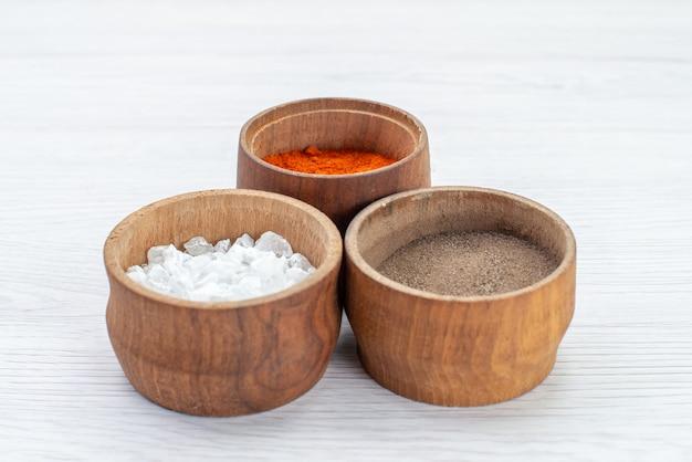 Vooraanzicht verschillende kruiden in kleine potten op wit bureau ingrediënt product voedselmaaltijd