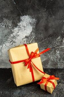 Vooraanzicht verschillende maten cadeautjes gebonden met rood lint op donkere geïsoleerde achtergrond