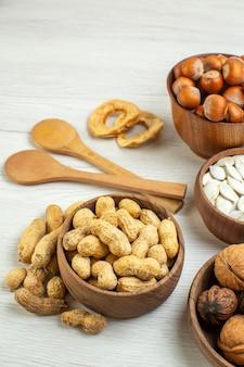 Vooraanzicht verschillende noten pinda's hazelnoten en walnoten op witte ondergrond