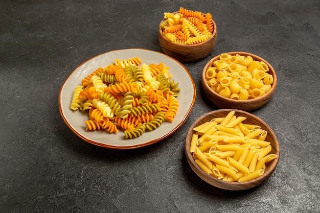 Vooraanzicht verschillende pasta samenstelling rauw product binnen platen op grijze ruimte