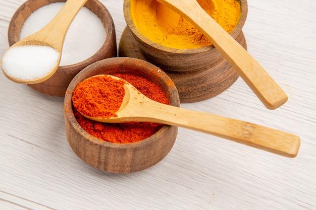 Vooraanzicht verschillende smaakmakers in kleine potten op een wit bureau peper kleur voedsel pittige hete foto