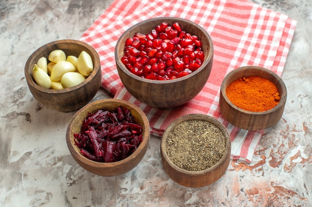 Vooraanzicht verschillende smaakmakers knoflook granaatappels en bieten op lichte achtergrond Gratis Foto