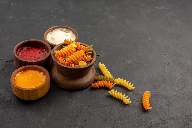 Vooraanzicht verschillende smaakmakers met rauwe pasta op donkere bureau pasta pittig eten maaltijd
