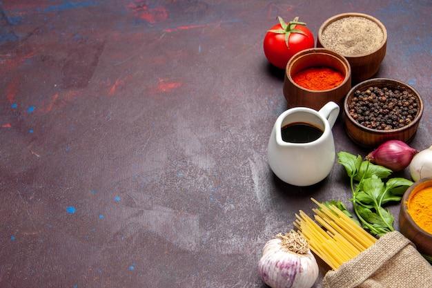 Vooraanzicht verschillende smaakmakers met rauwe pasta op donkere ruimte