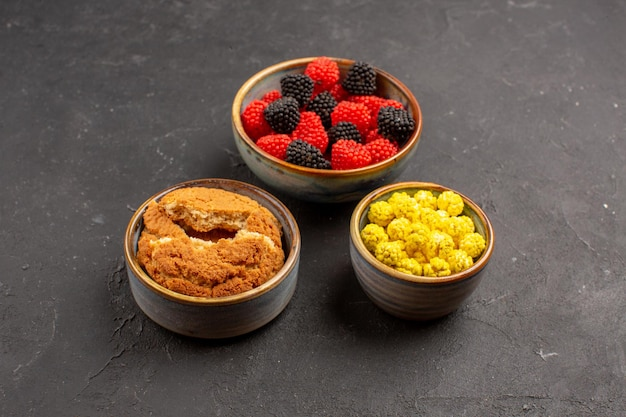 Vooraanzicht verschillende suikerconfituren in kleine potten op donkere achtergrond suikerspin goodie bonbon kleur bes