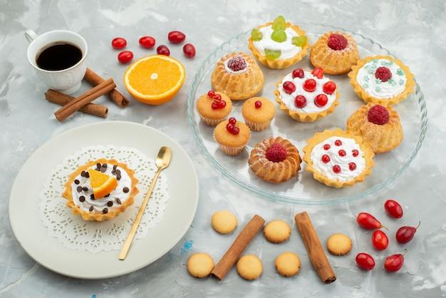 Vooraanzicht verschillende taarten met kaneel koekjes en kopje koffie op het lichte oppervlak suiker zoet fruit