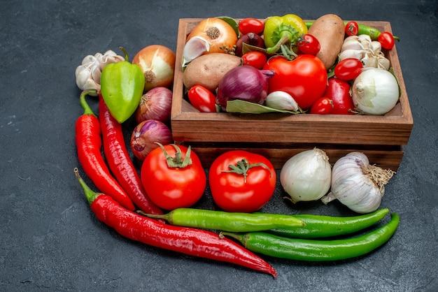 Vooraanzicht verschillende verse groenten op donkere tafel verse rijpe kleurensalade