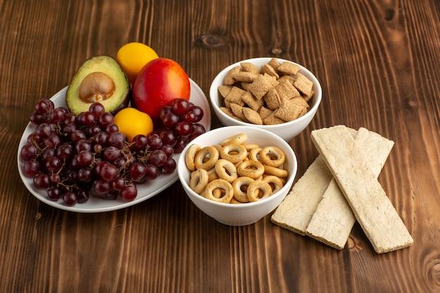 Vooraanzicht verschillende vruchten met crackers en koekjes op bruin houten bureau