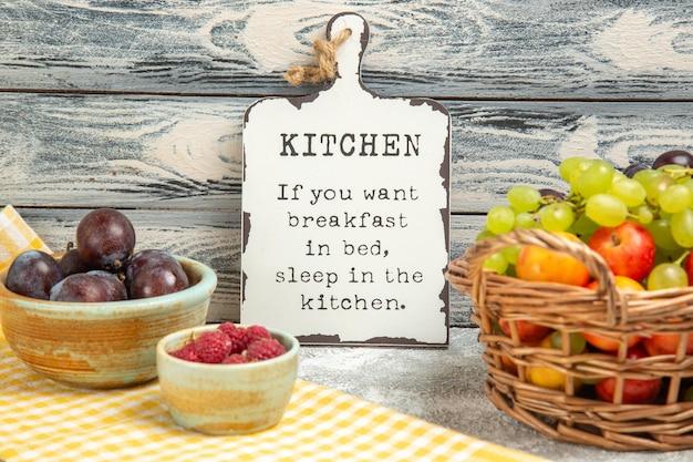 Vooraanzicht verschillende vruchten met grappig bureau op grijs zacht vers rijp fruit als achtergrond