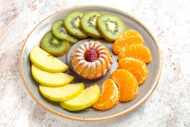 Vooraanzicht verschillende vruchten samenstelling vers en gesneden fruit met cake op witte achtergrond zacht rijp fruit gezondheid