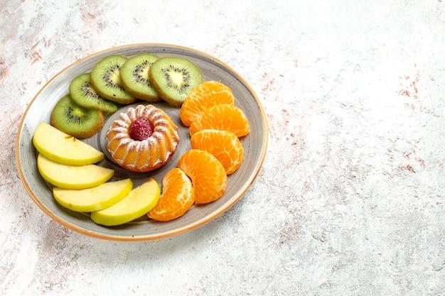 Vooraanzicht verschillende vruchten samenstelling vers en gesneden fruit met kleine cake op witte achtergrond zacht rijp fruit gezondheid