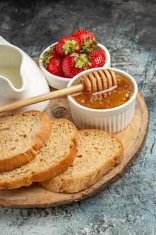Vooraanzicht verse aardbeien met brood en honing op donkere oppervlakte vruchten zoete gelei