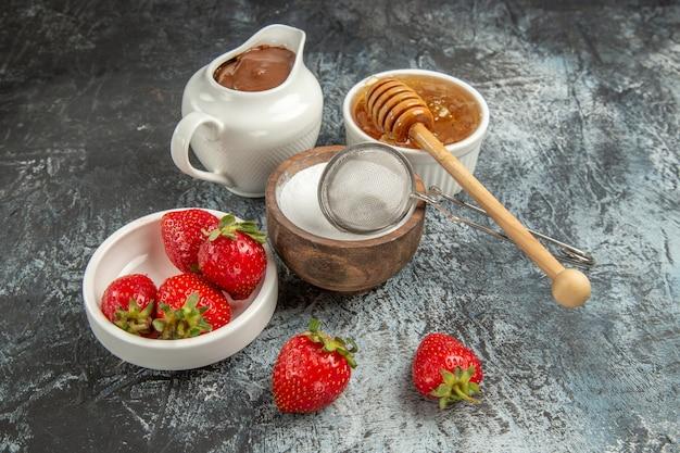 Vooraanzicht verse aardbeien met honing op donkere oppervlakte fruit bessen zoet
