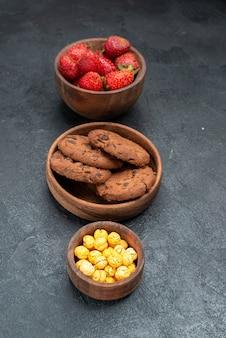 Vooraanzicht verse aardbeien met koekjes op donkere achtergrond