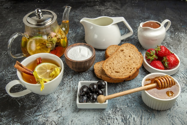 Vooraanzicht verse aardbeien met theebrood en honing op het donkere zoete voedsel van het oppervlaktefruit