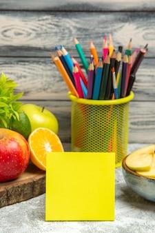 Vooraanzicht verse appels met gesneden sinaasappelen en potloden op de grijze rijpe zachte fruit verse appel als achtergrond