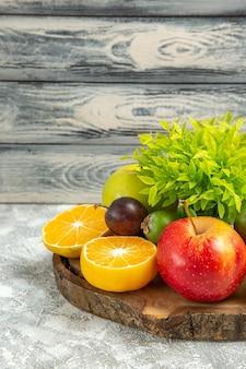 Vooraanzicht verse appels met gesneden sinaasappelen op de grijze achtergrond rijp zacht fruit verse appel
