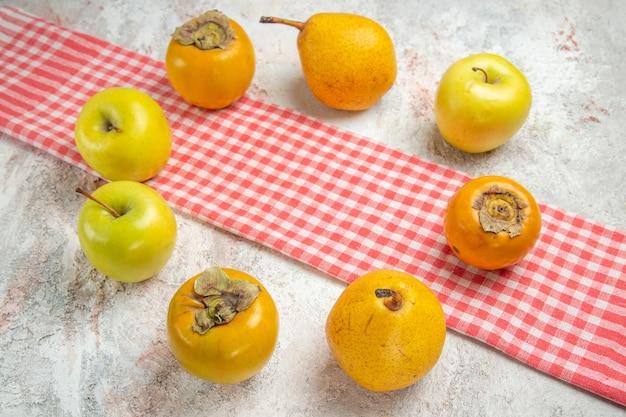 Vooraanzicht verse appels met kaki op de witte tafel fruit bessen gezondheid