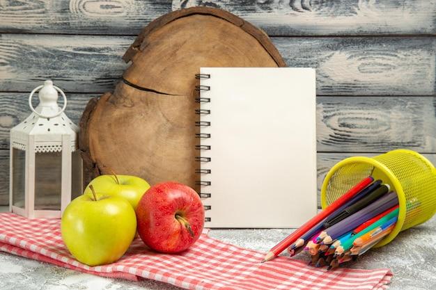 Vooraanzicht verse appels met kleurrijke potloden op grijs rijp zacht vers fruit als achtergrond