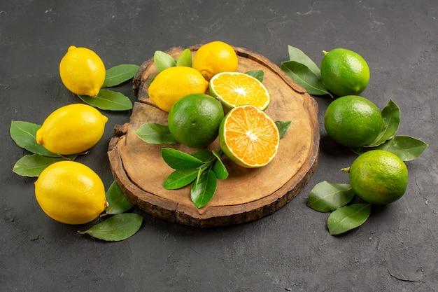 Vooraanzicht verse citroenen op de donkere achtergrond