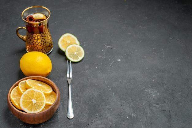 Vooraanzicht verse citroenplakken met thee op donkere achtergrond