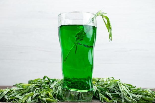 Vooraanzicht verse dragon drankje in lang glas met verse dragon bladeren op wit, dragon groen drink juice