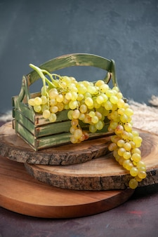 Vooraanzicht verse druiven groen en rijp fruit op het donkere oppervlak wijndruivenfruit rijpe verse boomplant
