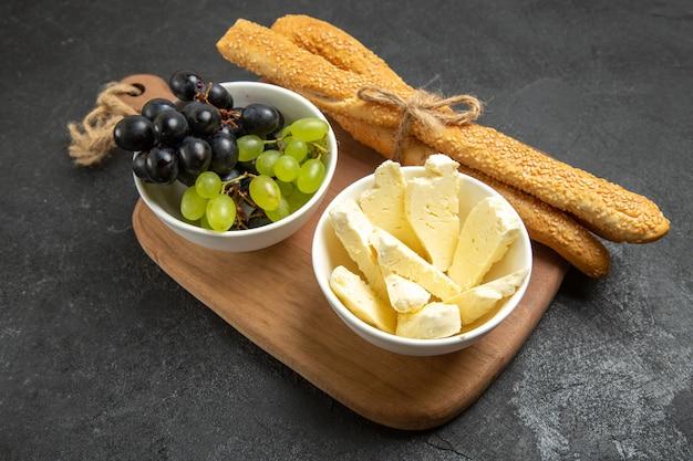 Vooraanzicht verse druiven met kaas en brood op de donkere achtergrond fruit zachte rijpe boom vitamine voedsel melk