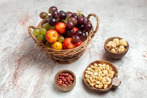Vooraanzicht verse druiven met noten op witte ruimte