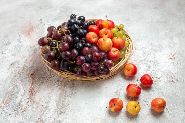 Vooraanzicht verse druiven met pruimen op witte ruimte
