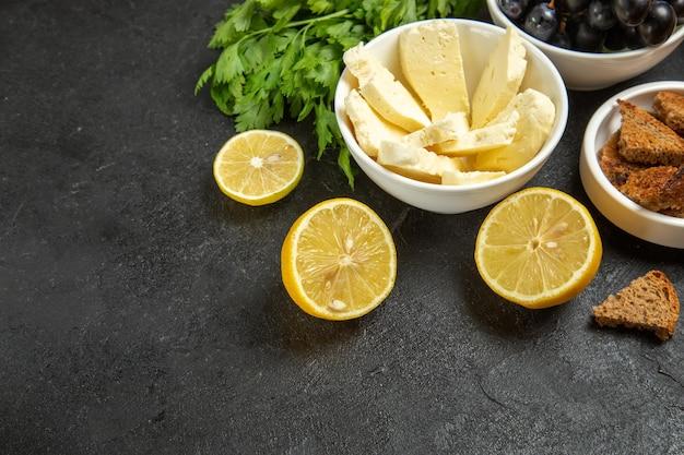 Vooraanzicht verse druiven met witte kaasgroenten en citroenplakken op de donkere achtergrondmaaltijd, ontbijtschotel, melkfruit