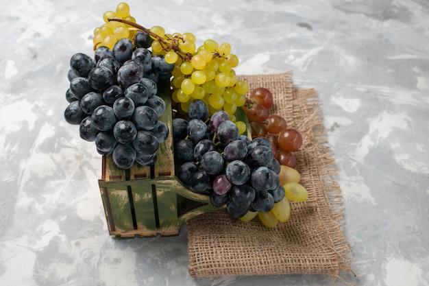 Vooraanzicht verse druiven sappig en zacht fruit op wit bureau