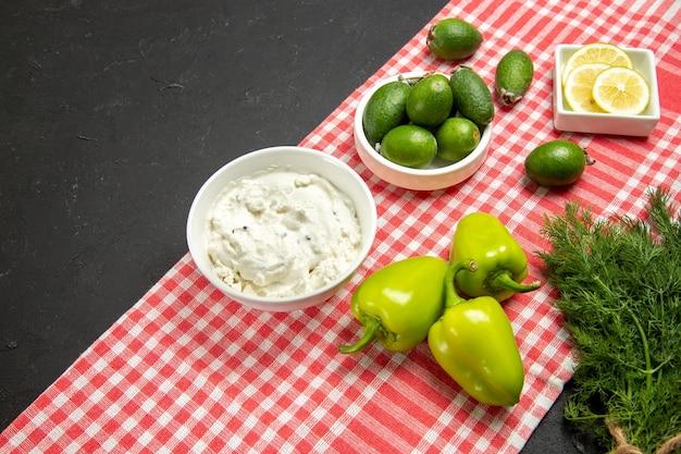 Vooraanzicht verse feijoa met greens en citroen op donkere oppervlaktefruit verse maaltijd fruit Gratis Foto