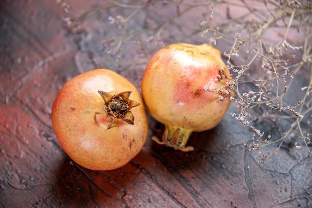 Vooraanzicht verse granaatappels gedroogde wilde bloementak op donkerrode geïsoleerde achtergrond