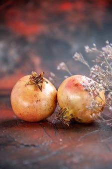 Vooraanzicht verse granaatappels gedroogde wilde bloementak op donkerrode vrije plaats