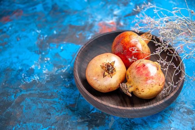 Vooraanzicht verse granaatappels in een kom op blauw
