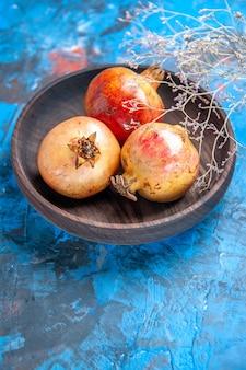 Vooraanzicht verse granaatappels in houten kom op blauw