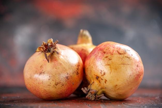 Vooraanzicht verse granaatappels op donkerrode geïsoleerde achtergrond