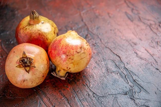 Vooraanzicht verse granaatappels op donkerrode houten grond met kopieerruimte