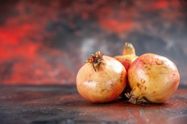 Vooraanzicht verse granaatappels op donkerrood met kopieerruimte