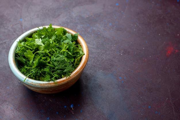Vooraanzicht verse greens in ronde kom op donkere tafel, groene verse groente