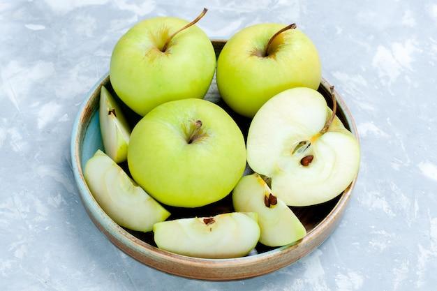 Vooraanzicht verse groene appels gesneden en hele vruchten op lichte oppervlakte fruit verse, zachte rijp voedsel vitamine