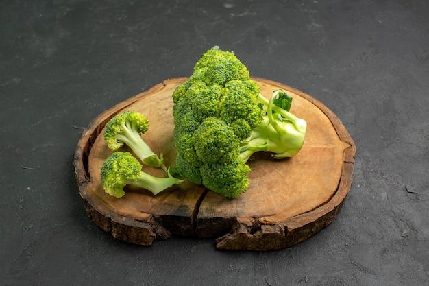 Vooraanzicht verse groene broccoli plant uit kool familie op donkere achtergrond