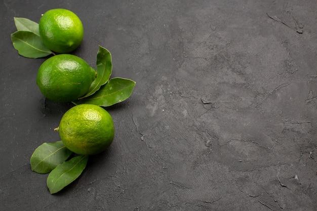 Vooraanzicht verse groene citroenen op donkere achtergrond
