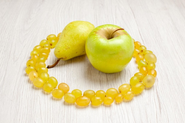 Vooraanzicht verse groene druiven met peer en appel op wit bureau fruit wijn zacht sap kleur